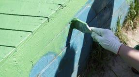 Der Maler malt die hölzerne Struktur Lizenzfreie Stockfotografie