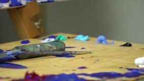 Der Maler ` s Arbeitsplatz, eine hölzerne Palette mit auf dem Farben eine Spachtel für das Zeichnen und eine Bürste liegt Kunst,  stock video