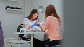 Der Manikürist hält Hände des Kunden im Schönheitssalon Lizenzfreies Stockbild