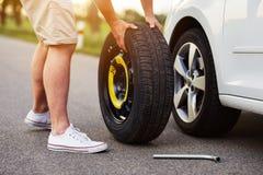 Der Mann ändert den Reifen zu einem defekten Auto stockfotografie