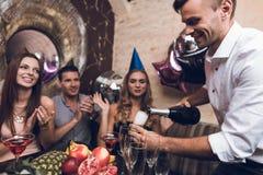 Der Mann öffnet Champagner zum Getränk mit seinen Freunden Sie sitzen im Verein am Tisch und im Rest nach dem Tanz stockfotografie