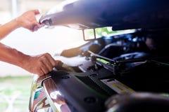 Der Mann öffnete die Haube des Autos und des Suchens nach einer Funktionsstörung stockfoto