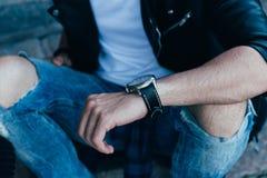 Der Mann überprüft die Zeit in den zackigen Jeans und in einer schwarzen Jacke Straßenart Mann ` s Hand mit einer Uhr Stockbilder