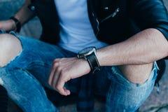 Der Mann überprüft die Zeit in den zackigen Jeans und in einer schwarzen Jacke Straßenart Mann ` s Hand mit einer Uhr betrachtet  Stockbilder