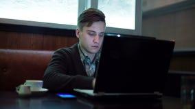 Der Mann arbeitet, indem er einen Laptop in einem Café verwendet stock video