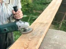 Der Mann arbeitet mit seinen Händen, reibt die Scheibe herum für den Schleifer, das Elektrowerkzeug für das Reiben und das Polier stockfotografie