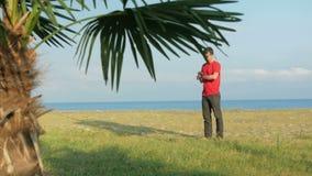 Der Mann auf dem felsigen Strand Palme im Vordergrund Der Mann verantwortlich für die intelligente Uhr auf eingehender Nachricht stock video footage