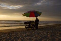 Der Mann auf dem Strand bei Sonnenuntergang Stockbild