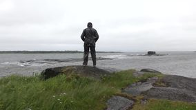 Der Mann auf dem Ufer des weißen Meeres im stürmischen Wetter stock video