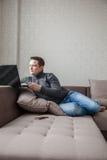 Der Mann auf einem Sofa mit Laptop Stockfotografie