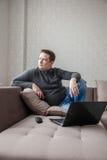 Der Mann auf einem Sofa mit Laptop Lizenzfreie Stockfotos