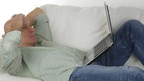 Der Mann, der auf Sofa Doing Business Using Laptop sitzt, machen enttäuschte Gesten stockfotografie
