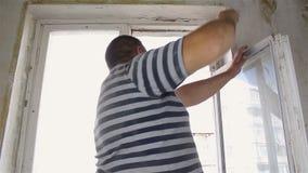 Der Mann baut das alte Fenster mit seinen Händen ab stock video footage