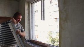 Der Mann baut das alte Fenster mit seinen Händen ab stock footage