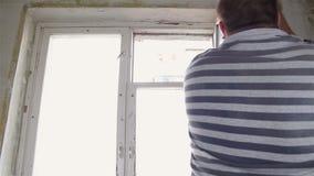 Der Mann baut das alte Fenster mit seinen Händen ab stock video