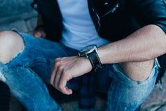 Der Mann betrachtet die Uhr überprüft die Zeit in den zackigen Jeans und in einer schwarzen Jacke Straßenart Mann ` s Hand mit ei Lizenzfreies Stockfoto