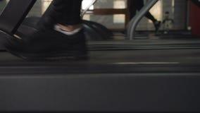 Der Mann bildet in der Turnhalle auf der Tretm?hle aus Nahaufnahmebetrieb auf den Tretm?hlenf??en stock footage
