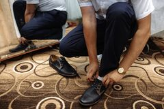 Der Mann bindet oben seinen Schuh auf einem Teppich stockfotos