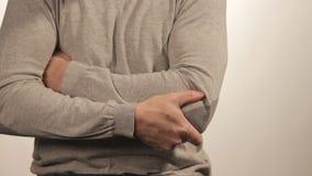 Der Mann, der den Ellbogen wegen der akuten Schmerz auf einem weißen Hintergrund massiert stock footage