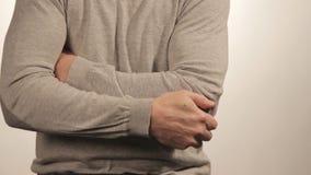 Der Mann, der den Ellbogen wegen der akuten Schmerz auf einem weißen Hintergrund massiert stock video