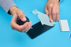 Der Mann, der den gebrochenen ausgeglichenen Glasschirmschutz für Smartphone ersetzt lizenzfreie stockfotos