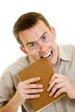 Der Mann in den Gläsern isst Buch. Stockbild