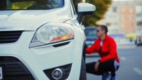 Der Mann in den Hintergrundblicken auf die Kratzer des Autos nach dem Unfall stock video