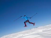 Der Mann in den Schneeschuhen springt in die Berge Lizenzfreies Stockbild