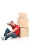 Der Mann, der auf Boden sitzt, ermüdete von beweglichen Kästen Stockbild