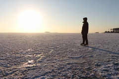 Der Mann, der auf den gefrorenen Fluss bei Sonnenuntergang eisläuft Stockbilder