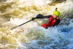 Der Mann, der auf den Stromschnellen des Gebirgsflusses supsurfing ist Lizenzfreies Stockfoto