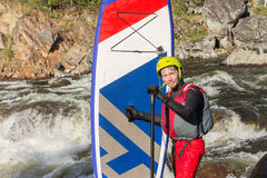 Der Mann, der auf den Stromschnellen des Gebirgsflusses supsurfing ist Lizenzfreie Stockbilder