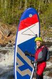 Der Mann, der auf den Stromschnellen des Gebirgsflusses supsurfing ist Stockfotos