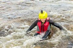 Der Mann, der auf den Stromschnellen des Gebirgsflusses supsurfing ist Stockfoto