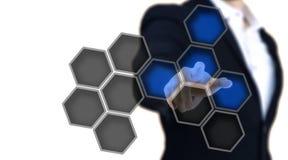 Der Mann, der auf a zeigt, glüht blauer Hexagonknopf Lizenzfreies Stockfoto