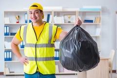 Der Mann, der das Büro säubert und Abfalltasche hält lizenzfreie stockbilder