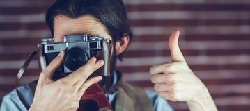 Der Mann, der Daumen zeigt, up Geste beim Fotografieren Stockfotografie