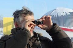 Der Mann, der in den Ferngläsern von einer Riesenradkabine schaut Stockfotografie