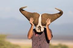 Der Mann, der den großen afrikanischen Büffelschädel trägt es hält, mögen eine Maske in der Natur auf afrikanischer Safari der wi Stockfotografie
