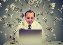 Der Mann, der den Laptop aufbaut das on-line-Geschäft macht GeldDollarscheine verwendet, wechseln unten fallen ein Europäisches G lizenzfreie stockbilder