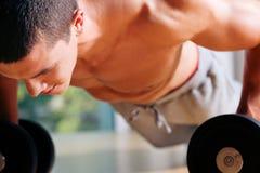 Der Mann, der in der Gymnastik trainiert - drücken Sie ups Lizenzfreie Stockfotos