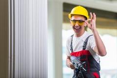 Der Mann, der die Wand mit Bohrgerätperforator bohrt Stockfotografie
