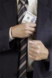 Der Mann, der Dollar setzt, verpacken in Tasche Lizenzfreie Stockfotografie