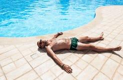 Der Mann, der durch das Pool sich sonnt Stockfotos