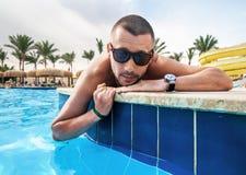 Der Mann, der durch das Pool sich sonnt Stockbilder