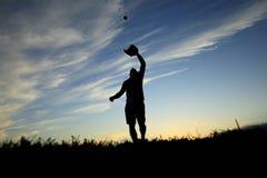 Der Mann, der durch den Sonnenuntergang silhouettiert wird, fängt gerade an Lizenzfreies Stockbild