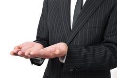 Der Mann, der einen Anzug mit seinen Händen trägt, öffnen sich, wie, Som zeigend oder halten Lizenzfreie Stockbilder