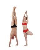 Der Mann, der Handstand tun und die Frau stehen auf einem Bein Stockbild