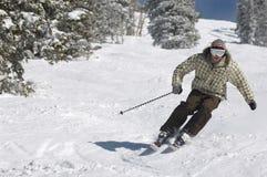 Der Mann, der hinunter Schnee Ski fährt, umfasste Steigung Stockbilder