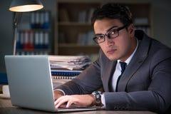 Der Mann, der im Büro für Überstunden bleibt Lizenzfreies Stockfoto
